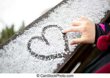 little girl drawing heart on snow - Closeup photo of little ...