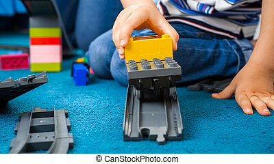 Closeup photo of little toddler boy playing woth toy train and railroad on carpet at playroom