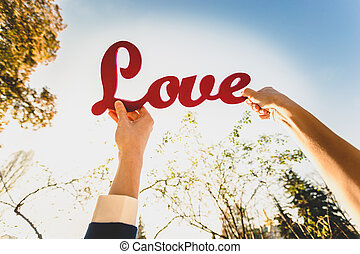 """man and woman holding red """"Love"""" sign"""