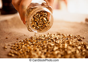 Closeup photo of man pouring out jar full of golden nuggets