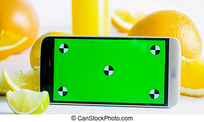 Closeup photo of mobile phone with green chromakey screen next to fresh fruits on white table. Perfect for inserting your own photo