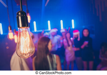 Closeup photo of old-fashioned light bulb making miracle atmosphere party crowd best friends on dance floor blurry focus wear dresses shirts pants night club