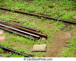 Closeup photo of old rusty and broken railroad rails lying on the ground