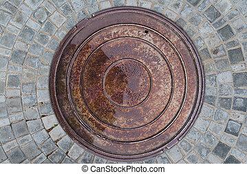 Closeup photo of Old Sewer rust manhole cover on the urban asphalt road. Rain scene.