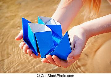 Closeup photo of paper ship in children hand