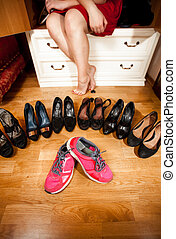 pink sneakers among black high heeled shoes at wardrobe -...