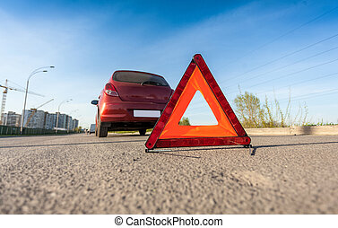 photo of red triangle sign on road next to broken car