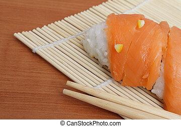 Closeup photo of salmon sushi and chopsticks on bamboo mat