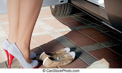 Closeup photo of sexy female driver changing high heel shoes to ballet flats before driving