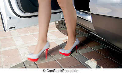 Closeup photo of sexy woman with long legs wearing high heels walking out of the car