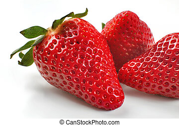 Closeup photo of three strawberries isolated on white background.