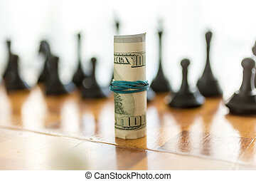 twisted american dollars on chessboard against black pieces