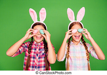 Closeup photo of two cute sweet lovely with open mouth long haired in checkered casual shirt outfit holding colorful eggs in hands isolated bright vibrant background