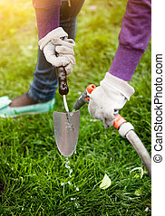 photo of woman cleaning garden tool with hosepipe