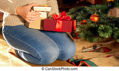 Closeup photo of woman sitting on floor and putting Christmas gifts and presents under Xmas tree