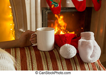 Closeup photo of woman sitting with cup of tea on sofa at fireplace