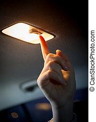 woman turning light on in car salon