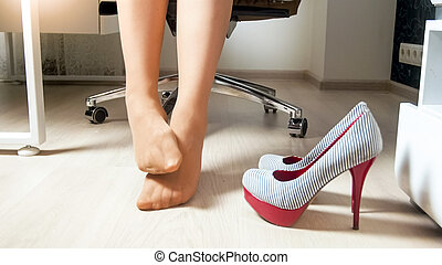 Closeup photo of young businesswoman massaging aching feet in pantyhose