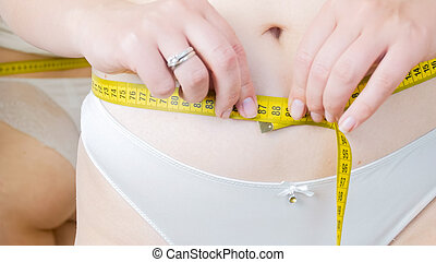 Closeup photo of young woman in white panties with measuring tape