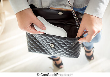 young woman putting menstrual pad out of handbag - Closeup ...