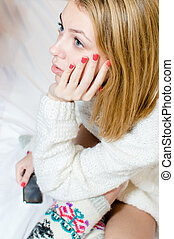 closeup picture of beautiful blond young woman blue eyes girl in knitted looking thoughtfully on white background