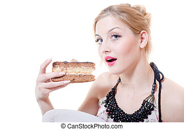 closeup picture of blue eyes beautiful blond young woman having fun eating alone large chocolate cake happy smiling & looking at camera on white background portrait
