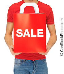 man's hands holding shopping bag