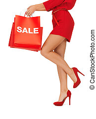 woman on high heels holding shopping bags - closeup picture...