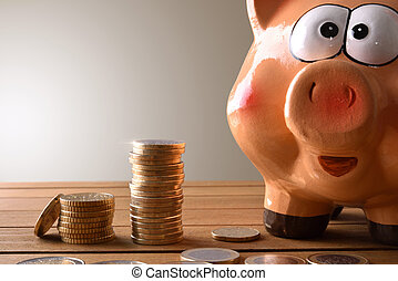 Closeup piggy bank with coins on wood table