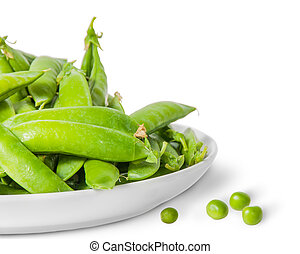 Closeup pile of green peas in pods in white plate