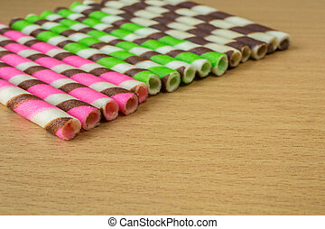 Closeup pink stripe wafer rolls on table.