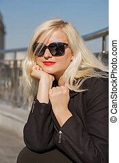 closeup, porträt, von, blond, modell, posierend, in, schwarz, mantel, trägt, sonnenbrille, auf, a, verwischt, stadt, hintergrund