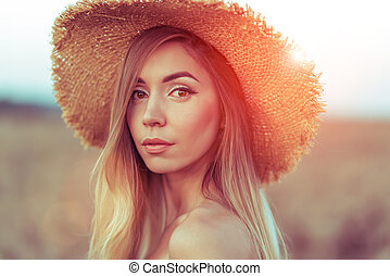 Closeup portrait, beautiful woman straw hat. In the summer on the nature of the tanned girl with long hair. Emotions of tenderness, smile and relaxing in the fresh air.