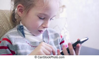 Closeup portrait child. Girl using mobile phone and smiling....