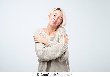 Closeup portrait, confident woman in warm sweater holding hugging herself, isolated white background.