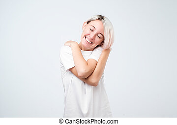Closeup portrait, confident woman in white t-shirt holding hugging herself, isolated white background.