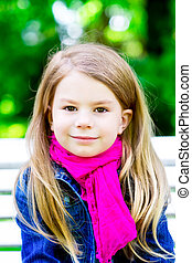 Closeup portrait of a beautiful smiling blond little girl in...