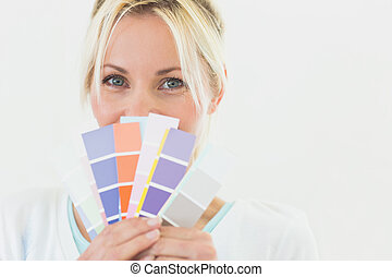 Closeup portrait of a beautiful woman holding color swatches...