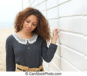 Closeup portrait of a beautiful woman walking with hand on wall