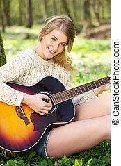 Closeup portrait of a beautiful young woman playing guitar