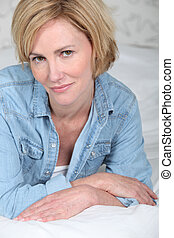 Closeup portrait of a blonde woman lying on a bed in a denim shirt