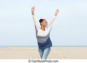 Closeup portrait of a carefree young woman with arms outstretched walking on the beach