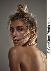 Closeup portrait of a charming blonde with a bun haircut