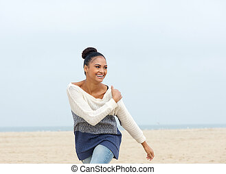 Closeup portrait of a cheerful carefree young woman walking on the beach