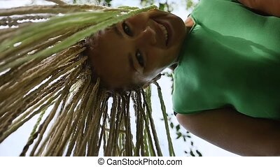 Closeup portrait of a cheerful young woman with white long dreadlocks. Slow motion