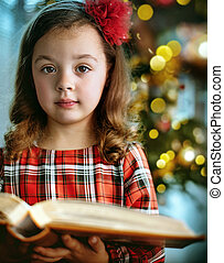 Closeup portrait of a cute, little girl holding a book