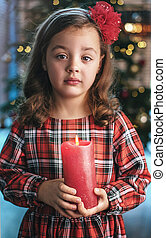 Closeup portrait of a cute, little girl holding a candle