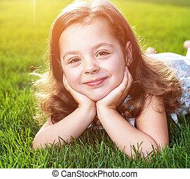 Closeup portrait of a cute little girl lying on a fresh lawn