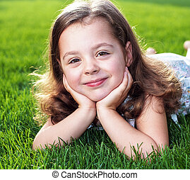 Closeup portrait of a cute little girl lying on a fresh lawn