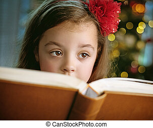 Closeup portrait of a cute, little girl reading a book